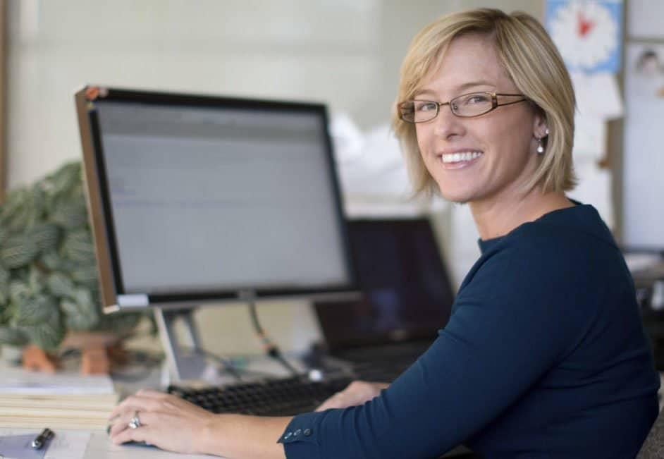 woman smiling in front of computer